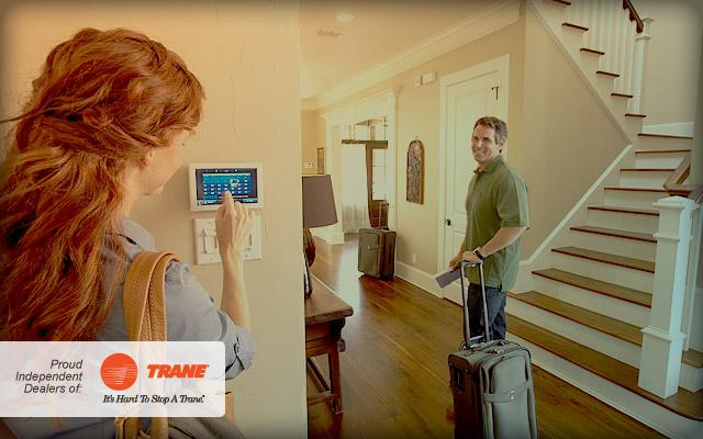 Couple setting ComfortLink™ thermostat before leaving for vacation